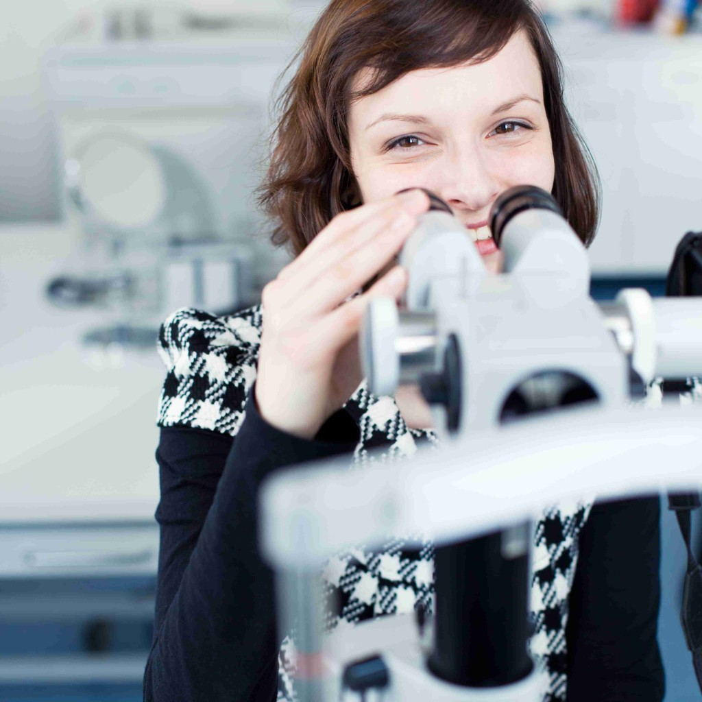 Optometry concept - portrait of a young pretty optometrist using